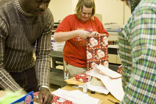 Members of the Services Support Division within the Directorate of Information Management-(l-r) Ron Alexander, Amanda Walker and Tim Morgan-get gifts ready for Christmas Cheer.
