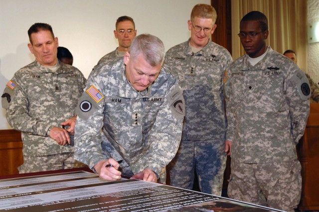 HEIDELBERG, Germany (Dec. 18, 2008) -- Gen. Carter F. Ham, commanding general of U.S. Army, Europe and Seventh Army, signs the Warrior Healthcare Covenant at USAREUR headquarters in Heidelberg, Germany, Dec. 18. The covenant is a committment to quality health care, assistance and a healing environment for Soldiers and their families, said Army Surgeon General Lt. Gen. Eric B. Schoomaker (second from right). Spc. Derraivius Strawder, a wounded Soldier from the Warrior Transition Unit in Baumholder, Germany (right), attended the ceremony as a representative of USAREUR's wounded warriors. Ham, who has a son-in-law attached to a Warrior Transition Unit, called the covenant an important symbol of the Army's commitment to Soldier care. Also pictured are USAREUR Command Sgt. Maj. Ralph Beam (left) and Brig. Gen. Keith W. Gallagher, USAREUR command surgeon and commander of the Europe Regional Medical Command.