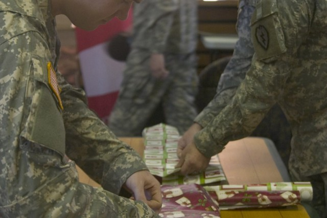 SCHOFIELD BARRACKS, Hawaii - Pvt. 1st Class Christopher Holliday (left) and Pvt. 1st Class Jamie McNerlin, 2-27 Infantry Regiment, wrap gifts to be sent to the Holy Family Home in Osaka, Japan. A tradition that started more than 50 years ago has continued as Soldiers and family members gather together to bring holiday cheer to young orphans.