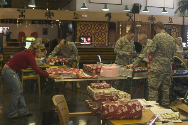 SCHOFIELD BARRACKS, Hawaii - Soldiers from the 27th Infantry Regiment, along with family members wrapped numerous gifts to be sent to Japan this holiday season. Through donations from Soldiers and the community, smiles will be seen from the faces of many children at the Holy Family Home in Osaka.