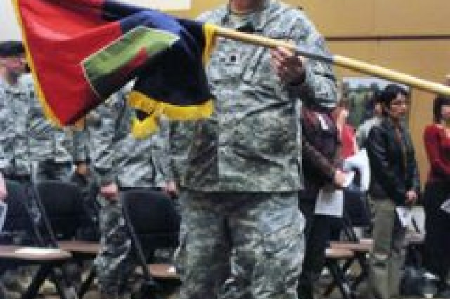 Lt. Col. Mark Childs uncases the Division Headquarters and Headquarters Battalion colors Dec. 12 during the activation ceremony. Childs is the new battalion commander of DHHB, the first headquarters battalion structured under the Army's new modular design.