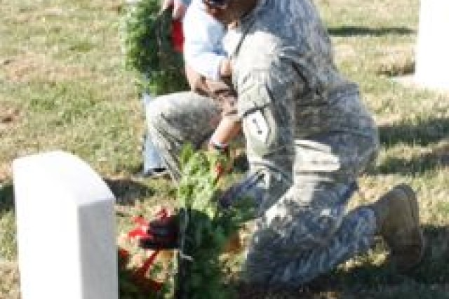 Capt. Rashad Fulcher, 1st Bn., 18th Inf. Regt., Rear Detachment, lays a wreath on a tombstone during the Fort Riley Wreaths Across America Dec. 13 at the Post Cemetery. More than 900 wreaths were donated to be placed during the ceremony.