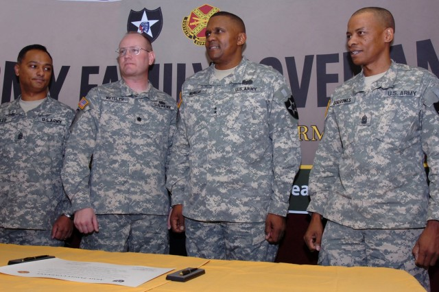 3.(from left to right) Command Sgt. Maj. Nidal Saeed, command sergeant major for Camp Casey, Lt. Col. Donald Meisler, garrison commander for Camp Casey, Maj. Gen. John W. Morgan III, commanding general for the 2nd Infantry Division and Command Sgt. Maj. Peter Burrowes, division Command sergeant major, signs the Army Family Covenant document during the ceremony held at the Pear Blossom Cottage 23 Dec. at Camp Casey.