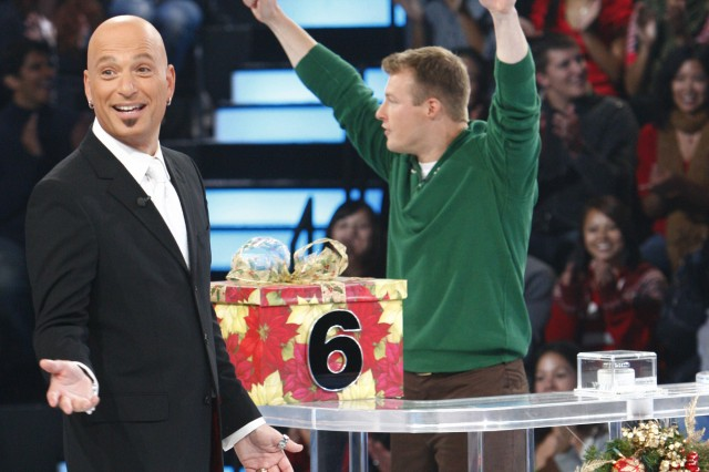 """Deal or No Deal"" host Howie Mandel gestures at the camera while Staff Sgt. Matthew Zedwick looks to his on-stage guests.  Zedwick said Mandel was a ""pretty nice guy,"" and was really excited to have newlywed Zedwick and wife Kristin on the show. The two-hour Christmas special will air at 8 p.m. EST, Dec. 25."
