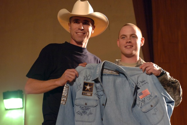 """Country music superstar Jamie Buckley presents a grateful Soldier with a denim jacket emblazoned with autographs from all of the """"2008 Sergeant Major of the Army Hope and Freedom Tour"""" performers at the Sustainer Theater at Joint Base Balad, near Balad, Iraq Dec. 21. This year's tour marked the 7th annual advent of the """"Hope and Freedom Tour"""", which brings many well-known entertainers to overseas to perform for deployed servicemembers. (U.S. Army photo by Pvt. 1st Class Jesus J. Aranda, Task Force Lightning Public Affairs)"""
