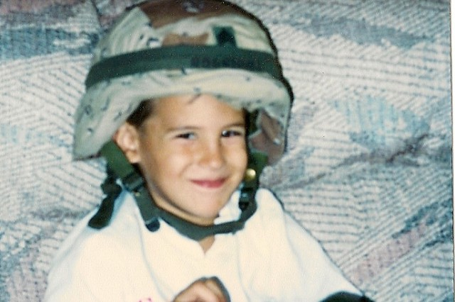 Spc. Jeremy Rodriguez, Headquarters and Headquarters Company, 1st Battalion, 21st Infantry Regiment, 2nd Stryker Brigade Combat Team, 25th Infantry Division, plays with his father's Kevlar and gloves when he was a child. Spc. Rodriguez is currently serving his 15-month tour in Iraq.
