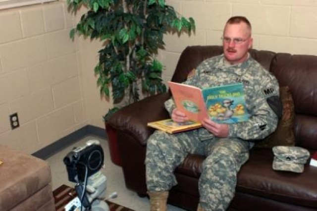 """Staff Sgt. Joseph James from Rice Lake, Wis., a military police officer with Headquarters and Headquarters Company, 2nd Special Troops Battalion, 2nd Brigade Combat Team, 1st Cavalry Division, reads """"The Ugly Duckling"""" while making a video for his children to see and hear him after he deploys. The videos are made through the United Services Organization's United Through Reading program."""