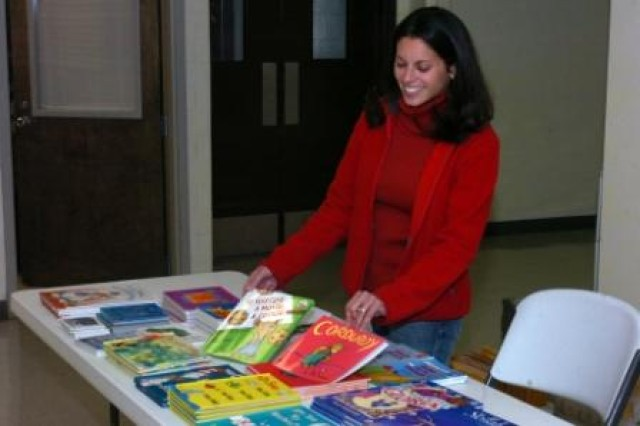 Lucy Limon, wife of a deployed Soldier and United Service Organization's volunteer, showcases books available as part of the USO's United Through Reading program for Soldiers preparing to deploy. Soldiers can read the books aloud and have their sessions recorded on DVD so their children can hear and see them after they have deployed.