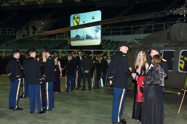 While waiting for the dinner portion of the winter formal to begin, Soldiers from the 1st Air Cavalry Brigade, 1st Cavalry Division, and their guests take in the atmosphere at the Bell County Expo Center in Belton, Texas, Dec. 17. The dinner was set with a background display of an AH-64D Apache attack helicopter and a UH-60 Black Hawk helicopter (right) - two 20 million dollar decorations - fitting for an Army Aviation unit.