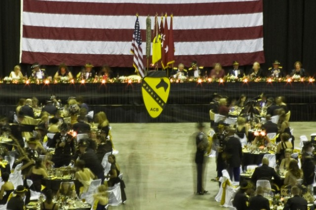 "Underneath the dome of the Bell County Expo Center in Belton, Texas, senior leaders of the 1st Cavalry Division and 1st Air Cavalry Brigade, with honored guest retired Gen. Dick Cody, former vice chief of staff of the Army, overlook Soldiers from the1st Air Cav. Bde. enjoying a catered dinner at tables adorned in gold and black - the First Team's colors. This was all part of the ""Warrior"" brigade's winter formal held Dec. 17."