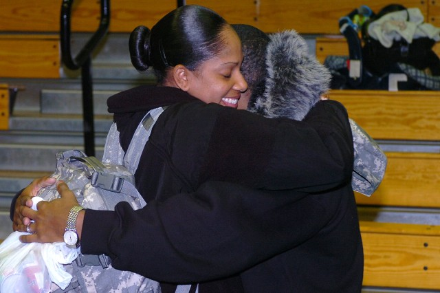 Sgt. Janel Bartley, a finance clerk with Detachment D, 230th Financial Management Company, hugs Devaughn Bartley during a deployment ceremony Dec. 21 at the Kieschnick Physical Fitness Center on Fort Hood. About 30 Soldiers from the 230th deployed to places in Kuwait and Qatar in support of Operation Iraqi Freedom.