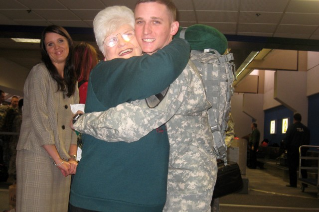 Pfc. Travis Kaufman, , 27th BSB, 4th BCT, 1st Cav. Div., hugs Shirley Cooker, a USO volunteer and member of the Mimosa Lane Baptist church, as Kaufman departs the Dallas Fort Worth Airport to return to Iraq.