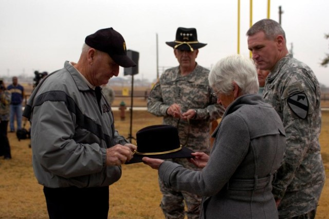 Brigadier General John (Mike) Murray, Deputy Commanding General (Maneuver), 1st Cavalry Division (far right) looks on as his father John Murray (far left) pins the star of Brigadier General on a Stetson held by his mother Janet (third from left) as General Pete Chiarelli, Vice Chief of Staff of the U.S. Army (center) observes during a promotion ceremony Dec. 23 at the 1st Cavalry Division Stables.
