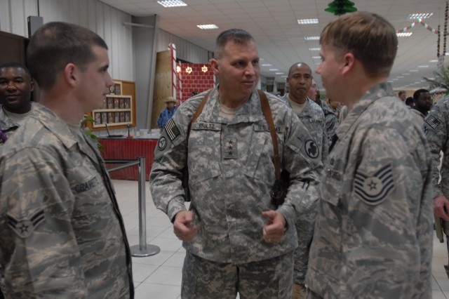 Lt. Gen. Jack Stultz speaks with Airman 1st Class David Charette and Tech. Sgt. Russell Sarkela from the 332nd Expeditionary Maintenance Group. While waiting in line for lunch at the Oasis dining facility at Joint Base Balad Dec. 25.