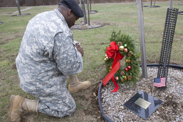 PICATINNY ARSENAL, N.J. - Chaplain's assistant Sgt. Andre L. Gambrell pauses for a prayer after laying a wreath for 1st Sgt. Christopher D. Coffin here Dec. 10. Coffin died in Iraq July 1, 2003. Gambrell placed the wreath on behalf of Coffin's family in Branchburg.