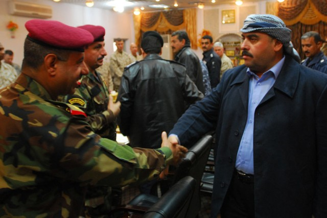 Gov. Mamoun Sami, right, Anbar provincial governor, greets representatives of the Iraq Army at a meeting in Anbar Dec. 20 to discuss the transfer of Sons of Iraq control from Coalition forces to the Government of Iraq.