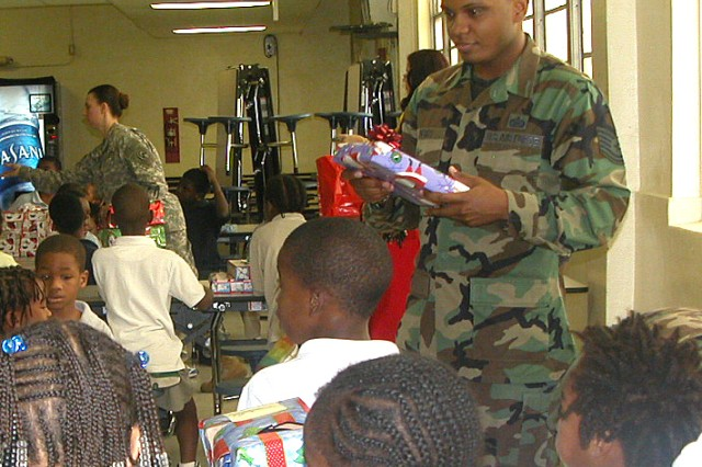 Dec. 18, 2008  -- AF TSgt. Marcus Perry and Staff Sgt. Amanda Douglas, US Southern Command Better Opportunities for Single Servicemembers president, distribute gifts donated by members of US SOUTHCOM to students at Liberty City Elementary School in Miami, Fla.
