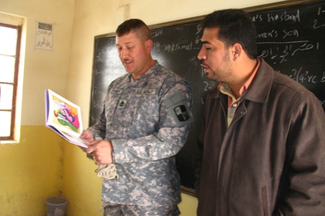 "Sgt. 1st Class Alexander Parker, Operations Sergeant, Civil Affairs, 287th Sustainment Brigade, reads a children's story to students at Al Saafy Elementary School, Al Habeb, Iraq, while interpreter Kamal translates his words into Arabic, Dec 23. His reading effort is part of the ""Read Iraq"" program which helps young Iraq students learning English as a second language to improve their listening and speaking skills."