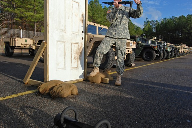 """Alpharetta, Ga. native Staff Sgt. John Adkerson, a combat engineer with Company A, Brigade Special Troops Battalion, 2nd Brigade Combat Team, 82nd Airborne Division, demonstrates how to conduct a forcible entry using a halligan tool during the BSTB's """"cross brief"""" training Dec. 15. The training was designed to give troopers in the battalion an understanding of all the different capabilities within the BSTB."""