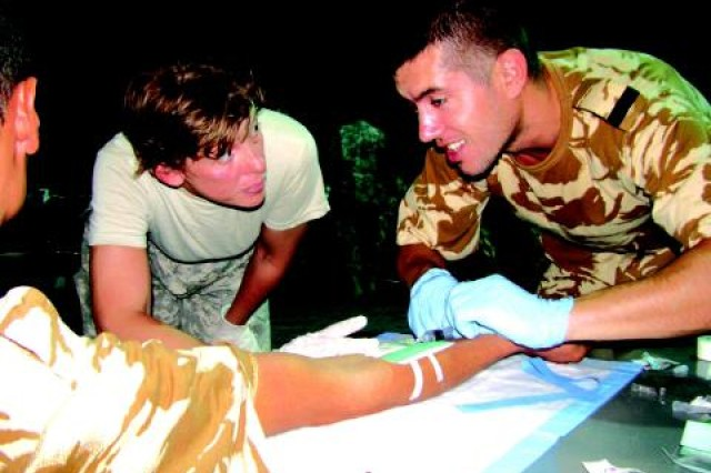 SGT Tammy Ellis of C Company, 27th Brigade Support Battalion, supervises as a Romanian soldier of the 341 Whitesharks Battalion starts an intravenous infusion during combat lifesaver training.