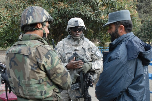 Soldiers of the 1st Infantry Division's Alpha Company, Special Troop Battalion, 3rd Brigade Combat Team, talk with the executive officer and captain of the Afghan National Police at the Shirazad District Center in Afghanistan's Nangarhar province.