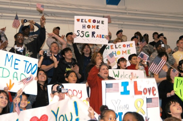 Family members cheer for than 130 Soldiers from the 11th Signal Brigade as they enter Barnes Field House, Fort Huachuca, Ariz.  Thunderbird Soldiers returned from a 15-month tour in Iraq.