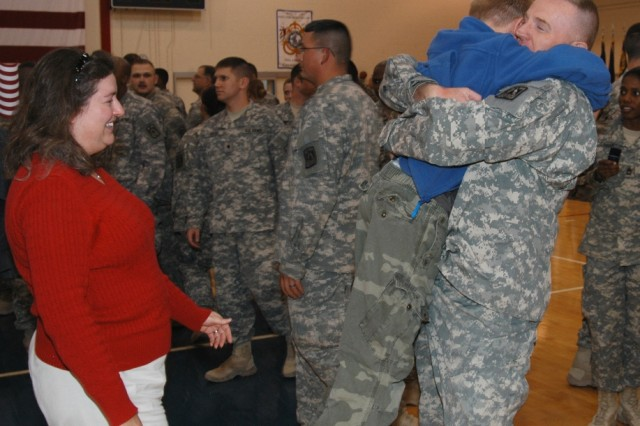Family members joyfully greet their Thunderbird Soldier after his return from a 15-month tour in Iraq.  More than 130 Soldiers from the 11th Signal Brigade returned home Dec. 24, to a heroes' welcome at Fort Huachuca, Ariz.