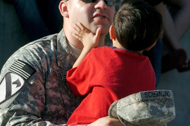 Spc. Jacob Ontiveros, a heavy equipment operator with Company A, 15th Brigade Support Battalion, 2nd Brigade Combat Team, 1st Cavalry Division, spends a few moments with his 5-year-old son Jonah outside Howze Theater Jan. 3. This is the Odessa, Texas's native's second deployment to Iraq.