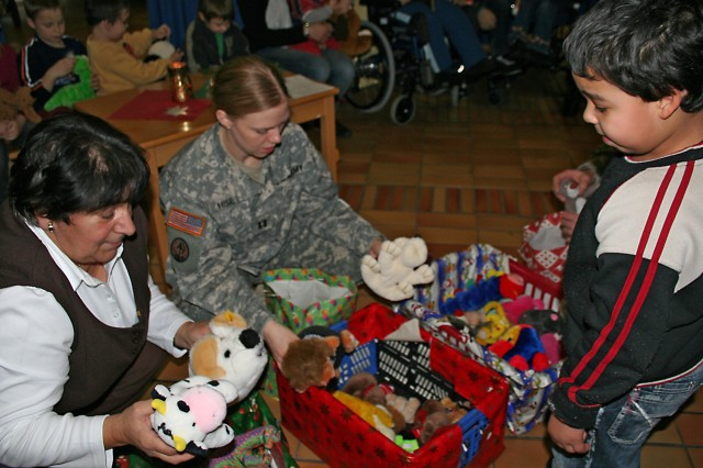 Bamberg KONTAKT Club members Barbara Kirchhof and Capt. Angela Hise hand out toys to children at Bertold-Scharfenberg-Schule Dec. 8. The school children entertained their benefactors with Christmas carols in German and English and treated them to kinderpunch and cookies before the day was over. The KONTAKTClub is an outreach group that  introduces American Soldiers to local traditions.