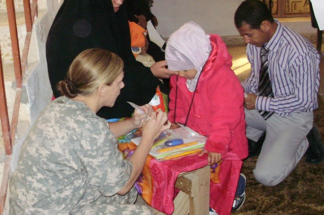 Capt. Lori August, 27th BSB, 4th BCT, 1st Cav. Div., and a native of Austin, Texas, gives an Iraqi student school supplies donated by families in the U.S.  Soldiers on COB Adder gave these supplies to the children after administering hearing exams to children from the al-Amal School for the Deaf, which is located in the town of Ar-Rumythan, about an hour north of Samawah in southern Iraq.