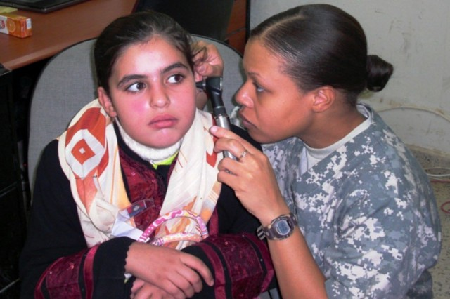 Capt. Ramona Toussaint, 27th BSB, 4th BCT, 1st Cav. Div., and a native of Brooklyn, N.Y., inspects an Iraqi child's ear. Approximately 15 Samawa schoolchildren received their first hearing exams Dec 28.