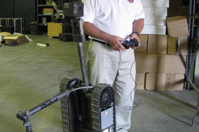 """Retired Marine Lt. Col. Norm Root demonstrates how the Fastac robot stands in """"Prairie Dog"""" position to see with its camera over a barrier. He is a contractor working for the Robotic Systems Joint Project Office, which is moving from Redstone Arsenal to Detroit Arsenal in Warren, Mich."""