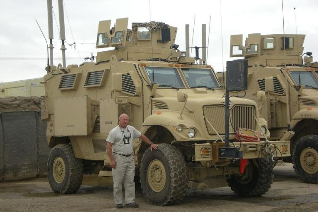 Norm Root stands beside an MRAP (Mine Resistant Ambush Protected) vehicle used by Marines in Iraq. The MRAP is designed to survive improvised explosive device attacks and ambushes. In June 2008, it was reported that roadside bomb attacks and fatalities are down almost 90 percent partially due to MRAPS. Root's training mission in Iraq also gave him opportunities to see how military technology and the country of Iraq has changed since 2004, when he was a Marine deployed to Fallujah.