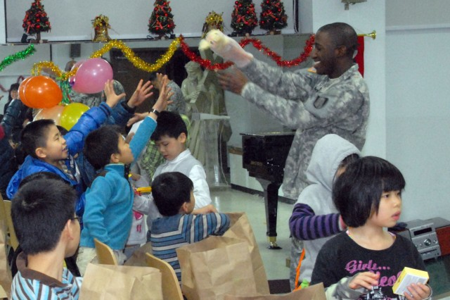 Spc. Charles Davis, 304th Sig. Bn., passes out toys to children at Myung-Jin Orphanage during a brief visit Jan. 7.