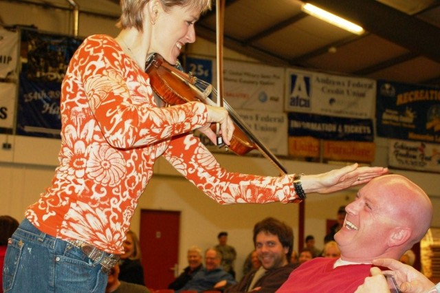 USAG Schinnen, NETHERLANDS – Wireless prank, fiddler style. Renae Claveria finds U.S. Air Force Senior Master Sgt. Marion Diggers, an Airman assigned to the NATO Air Base in Geilenkirchen, Germany, and apparently takes a 'shine' to him. Claveria, who roamed the audience with a wireless fiddle during her sizzling solos, made the fiddle strings squeak as she touched Digger's scalp, adding a special touch of fun to all who attended a performance by Thom Shepherd and the Nashville Songwriters Band to service and family members assigned to the Tri-Border region of Germany, Belgium and the Netherlands Jan. 7, 2009. (USAG Schinnen Army Public Affairs)