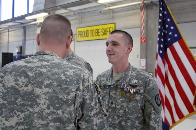 Maj. Andrew Risio, Charlie Company (Air Ambulance) of the 214th Aviation Regiment, awards the Combat Medic Badge to Sgt. Billy Raines during a welcome home ceremony Dec. 11 at the Landstuhl Heliport, located near the Landstuhl Regional Medical Center in Germany.