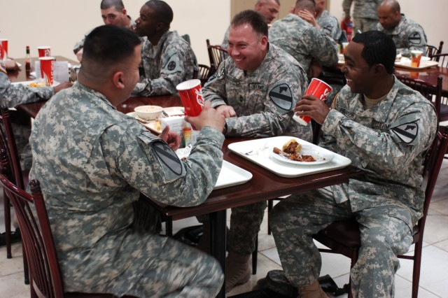 Soldiers from 2nd Brigade Combat Team, 1st Cavalry Division, enjoy lunch at the dining facility at Camp Buehring, Kuwait. The camp's dining facility has an assortment of food including a Salad bar, potato bar, various drinks and choices for entrees. The Soldiers will be able to enjoy the facilities while in Kuwait waiting to move forward into Iraq.