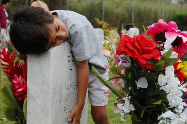 <p>SCHOFIELD BARRACKS, Hawaii - Six-year-old Caleb Samson wraps his arms around the headstone of his grandfather, James Clotildo Paraz Anguay, at Schofield Barracks Post Cemetery. Samson and his family attended the Memorial Day celebration, May 26, 2008, to honor and celebrate the memory of his grandfather and all men and women of the armed forces who have lost their lives.</p><p>(Editor's Note: This photo was run in conjunction with a 2008 Year in Review article in the <i>Hawaii Army Weekly</i>, U.S. Army Garrison-Hawaii's post newspaper.)</p>