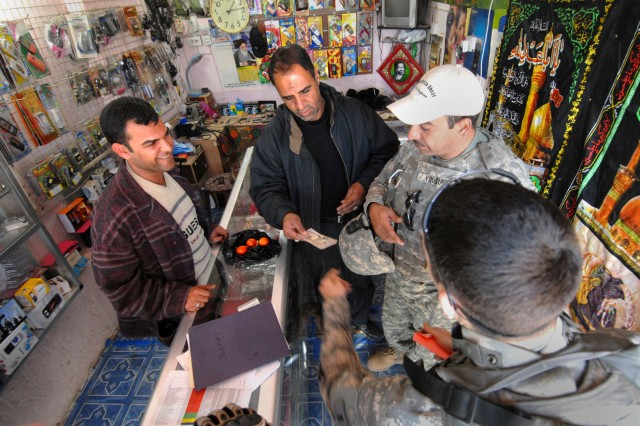 1st Lt. Matthew Valkovic, front, along with an interpreter, meet with a local shop owner in the Shulla neighborhood of northwest Baghdad, Jan. 8, 2009. Valkovic is assigned to the 1st Infantry Division's 1st Combined Arms Battalion, 18th Infantry Regiment, 2nd Heavy Brigade Combat Team.