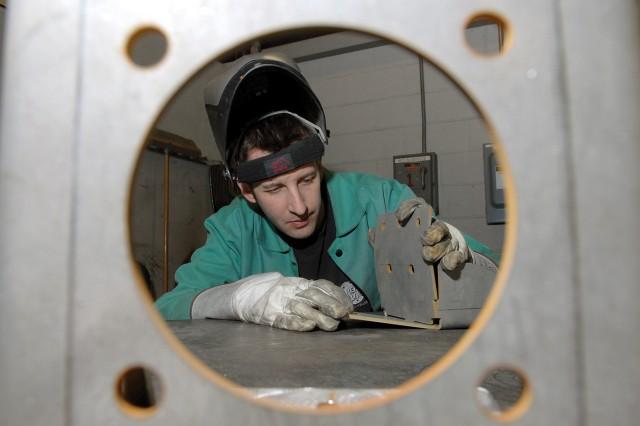 Trevior Gruber, welding worker, assembles a Duke antenna pull-down bracket for an MRAP.