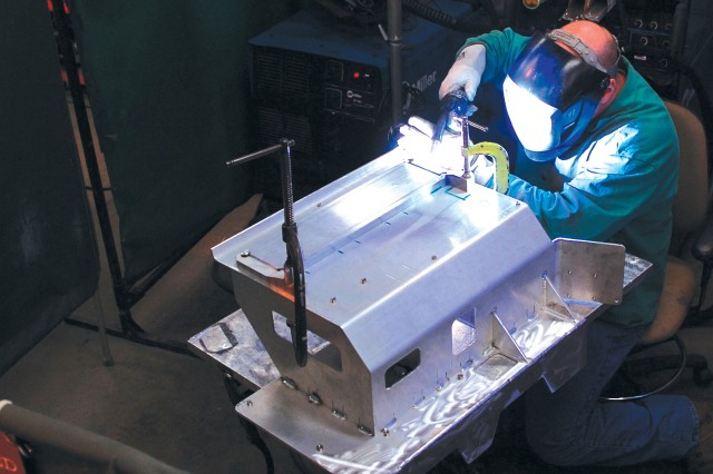 Thomas Kanios, welding worker, welds lower mounts to a BFT rack.