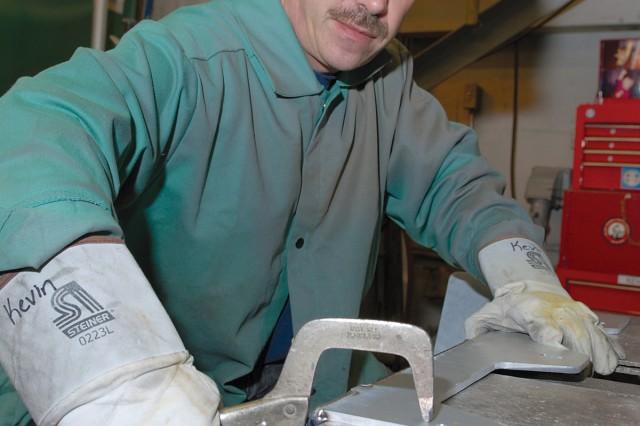 Kevin Handelong, welding worker, preps the top shelf of a BFT rack before welding.