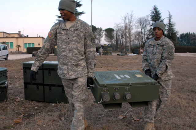 Spc. Hilliard Ladd, 21, of Fort Wayne, Ind. and Sgt. Lisa Davis, 22, of St. Louis, Mo., carry boxes of communication gear in the bitter cold during Lion Focus, a command exercise conducted by SETAF-U.S. Army Africa.