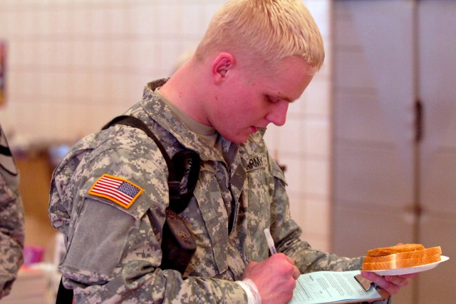 Prior to his flight, Boise, Idaho native Pfc. Michael D. Olsen, a Soldier with Headquarters and Headquarters Company, 1st Battalion, 8th Cavalry Regiment, 1st Cavalry Division, takes time to fill out a prayer request form provided by the members of a local church Jan. 9 at Fort Hood Texas. Soldiers could also find spiritual literature and keepsakes to carry along with them during their deployment.