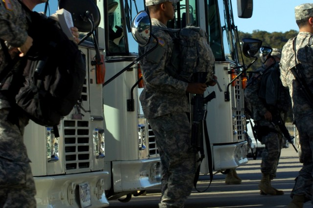 Prior to climbing on flights headed for a 12-month deployment to Iraq, Soldiers from the 1st Cavalry Division depart buses with weapon in hand at Robert Gray Army Air Field on Fort Hood, Texas Jan. 8.
