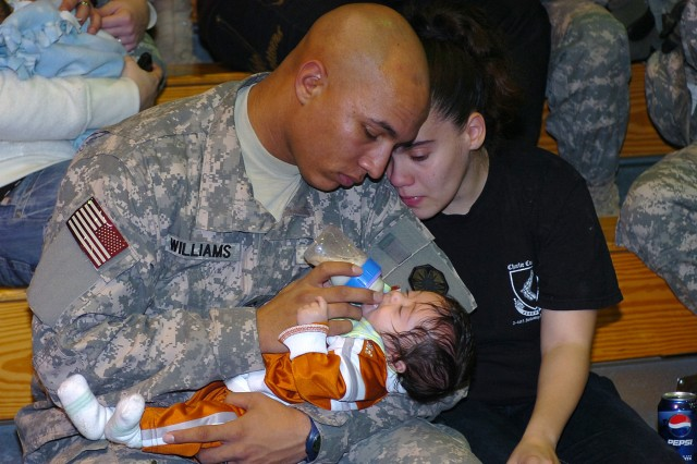 "Pfc. Anthony Williams, a Cliffwood, N.J., native and truck driver with the 154th Transportation Company, 180th Transportation Battalion, 15th Sustainment Brigade, feeds his 4-month-old daughter with his wife during a deployment ceremony Dec. 31, 2008, on Fort Hood, Texas. Williams and about 450 Soldiers from the 180th deployed to either Iraq or Afghanistan during the closing days of 2008. <br><br>Read more at:<br> <a href=""http://www.army.mil/-news/2009/01/07/15589-sustainment-soldiers-deploy-to-iraq-afghanistan/index.html"" target=""_blank"">Sustainment Soldiers deploy to Iraq, Afghanistan</a>"