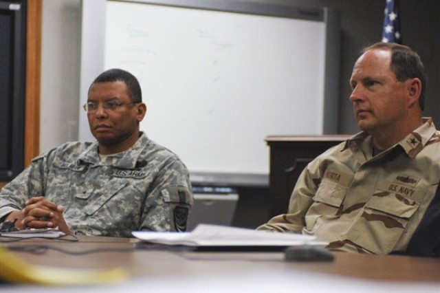 Army Brig. Gen. Sanford Holman, vice commander of U.S. Joint Forces Command's Joint Warfighting Center, and Navy Rear Adm. Anthony Kurta, Combined Joint Task Force Horn of Africa's prospective commander, discuss a mission rehearsal exercise,