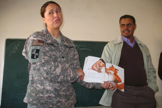 Sgt. Teresa Perrin, a patient administrator for the 287th Brigade Surgeon staff, puts on a sad face while reciting a children's story in English for students at Al Ashyabb school. Jan. 12, while interpreter Mansour looks on with amusement.