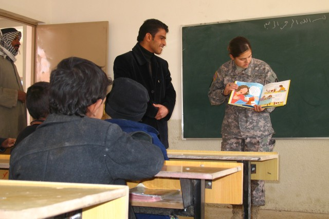 With assistance from interpreter Haider, Spc. Cassandra Miller, a supply specialist with the 287th Sustainment Brigade, reads a children book to Iraqi students at Al Ashyabb school, Jan. 12.