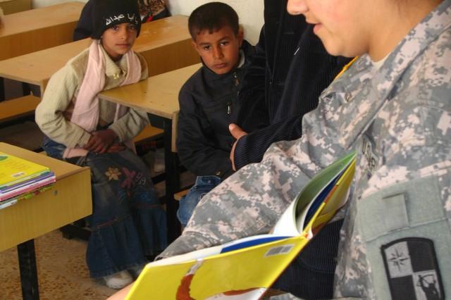 "Al Ashyabb school children listen to 287th Sustainer Spc. Cassandra Miller reading of a children's book in English as part of the ""Read Iraq program, Jan. 12."